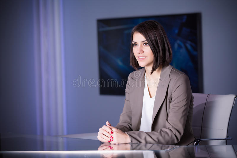 Young beautiful brunette television announcer at studio during live broadcasting.Female TV director at editor in studio. royalty free stock image