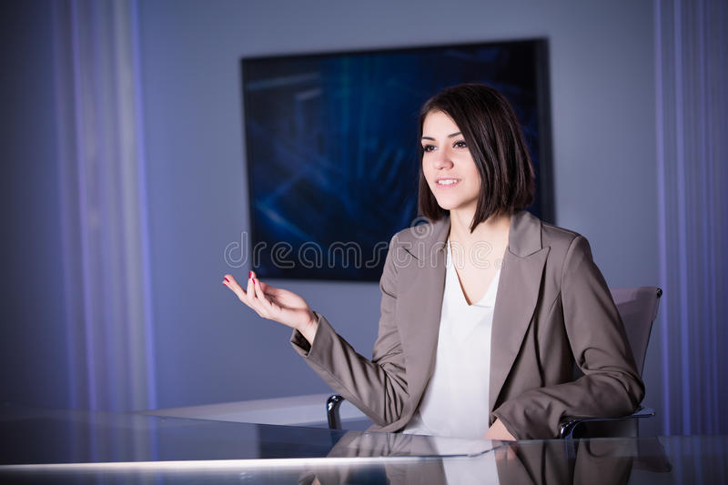 Young beautiful brunette television announcer at studio during live broadcasting.Female TV director at editor in studio. stock photo