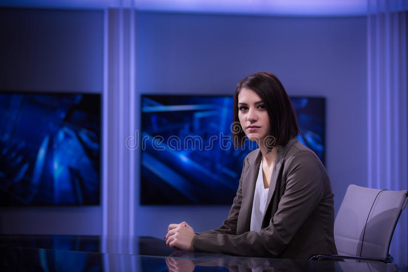 Young beautiful brunette television announcer at studio during live broadcasting.Female TV director at editor in studio. royalty free stock photos