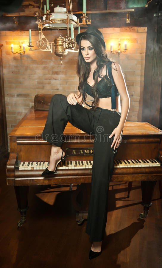 Young beautiful brunette woman in black male trousers, hat and braces sitting on a piano in vintage scenery. Romantic mysterious. Young lady with black bra stock photo