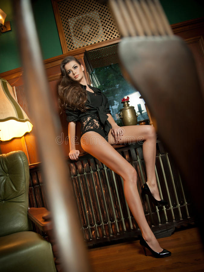 Young beautiful brunette woman in black tight fit body posing sensual in vintage scenery. Romantic mysterious young lady. With long legs in luxurious interior royalty free stock photos