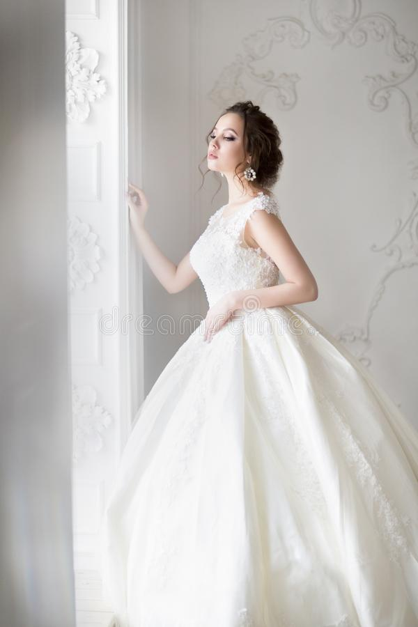Beautiful brunette woman with bouquet posing in a wedding dress. Young beautiful brunette woman with bouquet posing in a wedding dress royalty free stock photo
