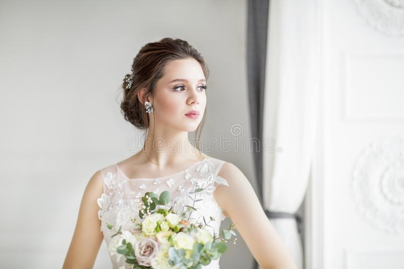 Beautiful brunette woman with bouquet posing in a wedding dress royalty free stock images