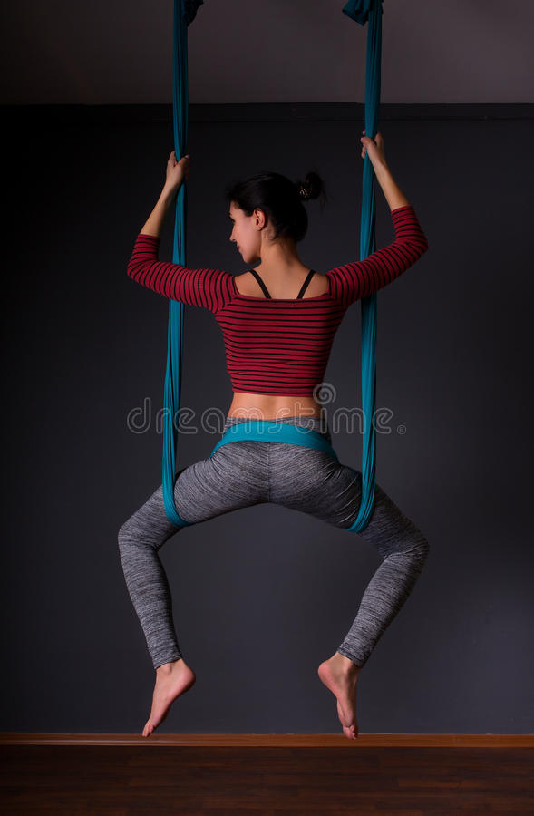Young beautiful brunette woman doing fly yoga. Sitting in hammock with namaste gesture. Wellness concept. Young beautiful woman doing fly yoga. Sitting in royalty free stock photo