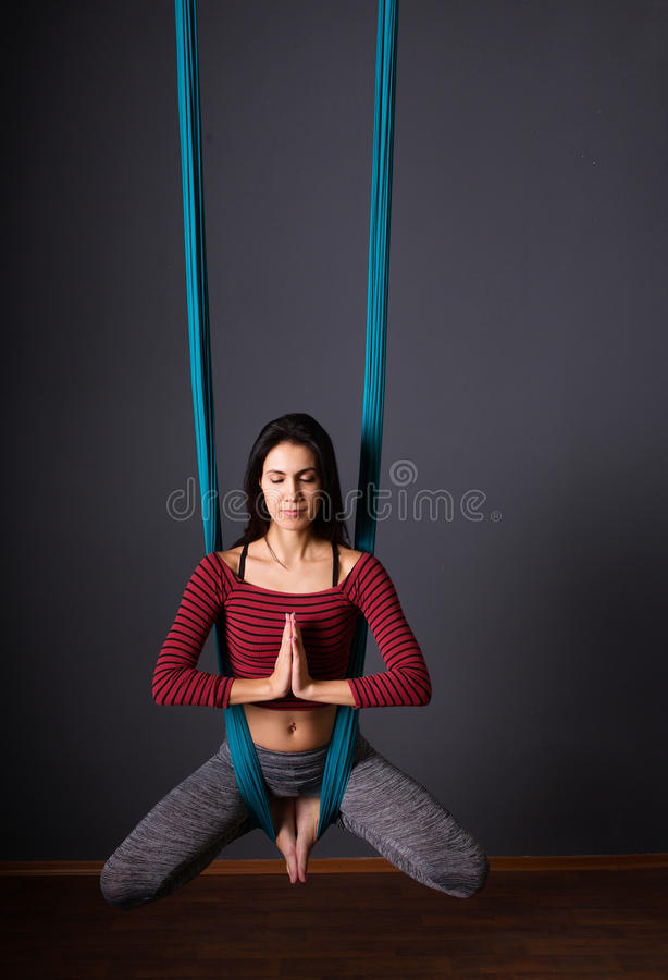 Young beautiful brunette woman doing fly yoga. Sitting in hammock with namaste gesture. Wellness concept. Young beautiful woman doing fly yoga. Sitting in stock images