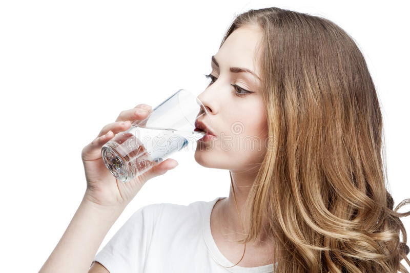 Young beautiful brunette woman drinking water royalty free stock photography
