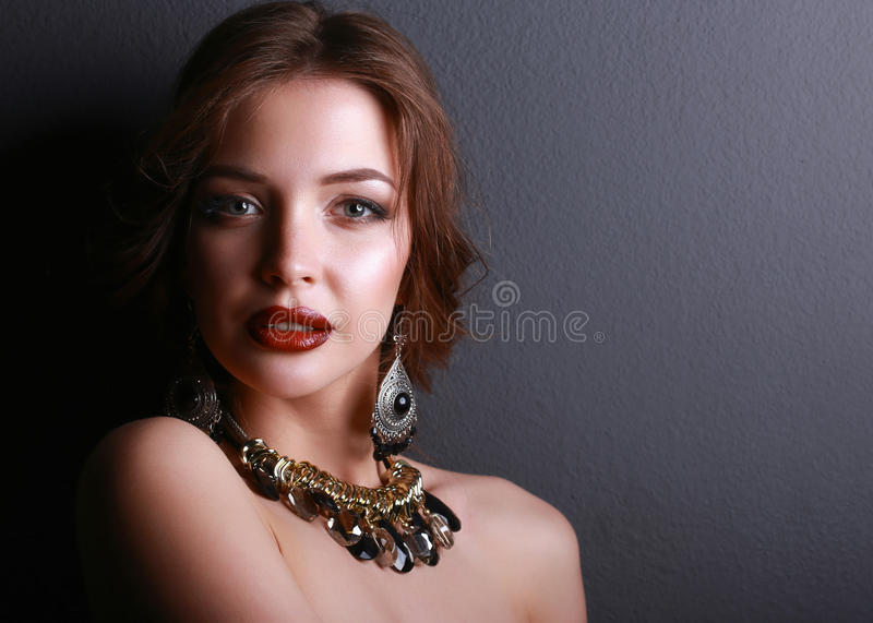 Young beautiful brunette woman in ear-rings, beads royalty free stock image