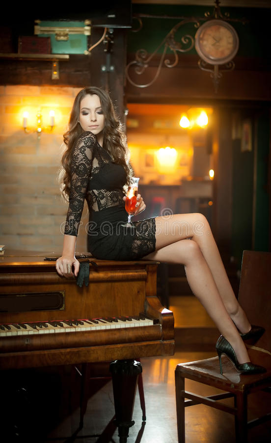 Young beautiful brunette woman in elegant black dress sitting provocatively on vintage piano. Sensual romantic lady with long hair. Young beautiful brunette stock images