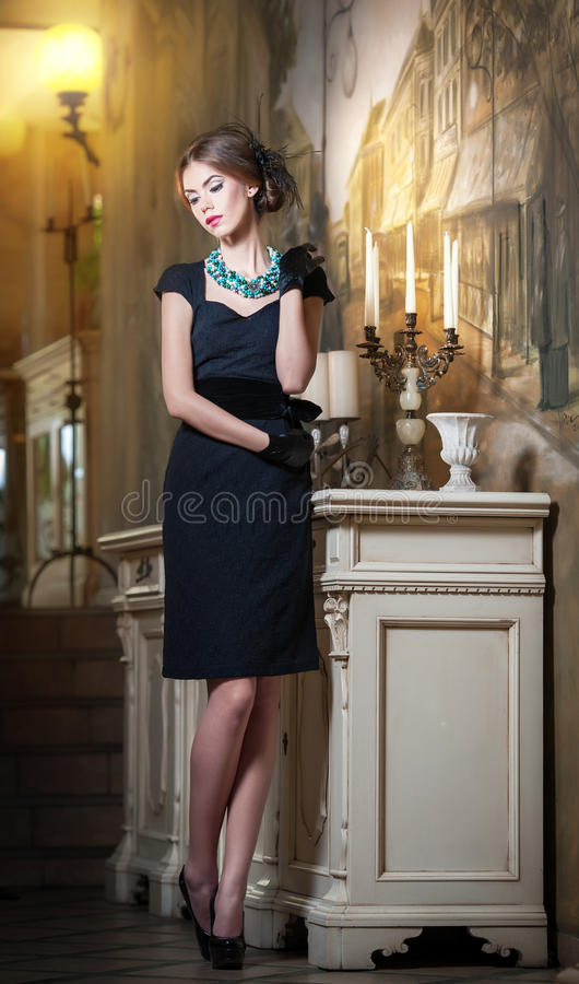 Young beautiful brunette woman in elegant black dress standing near a candlestick and wallpaper. Sensual romantic lady. With creative hairstyle on high heels in royalty free stock images