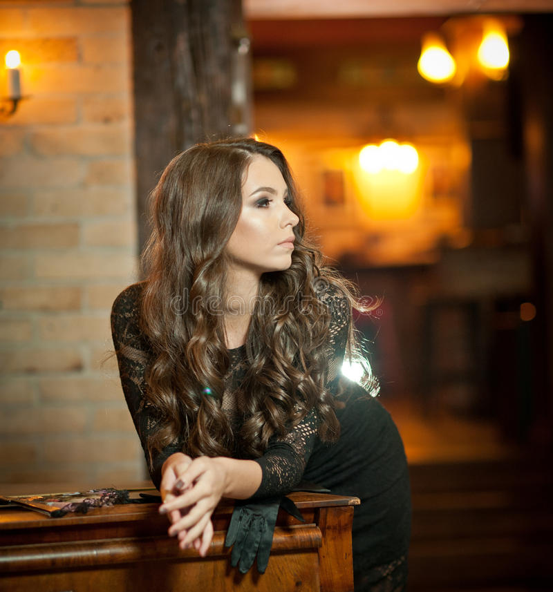 Young beautiful brunette woman in elegant black dress standing near a vintage piano. Sensual romantic lady with long dark hair. In luxurious interior royalty free stock photo