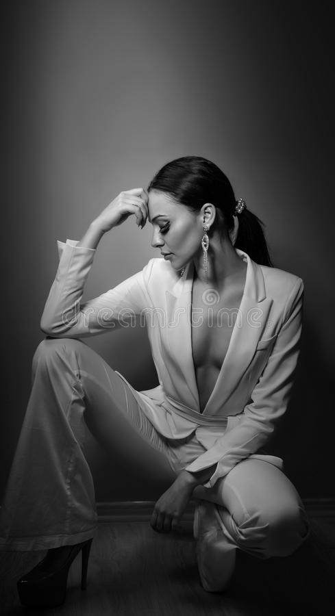 Young beautiful brunette woman in elegant white suit with trousers sitting. Seductive dark hair girl posing, studio shot. Elegant royalty free stock photography