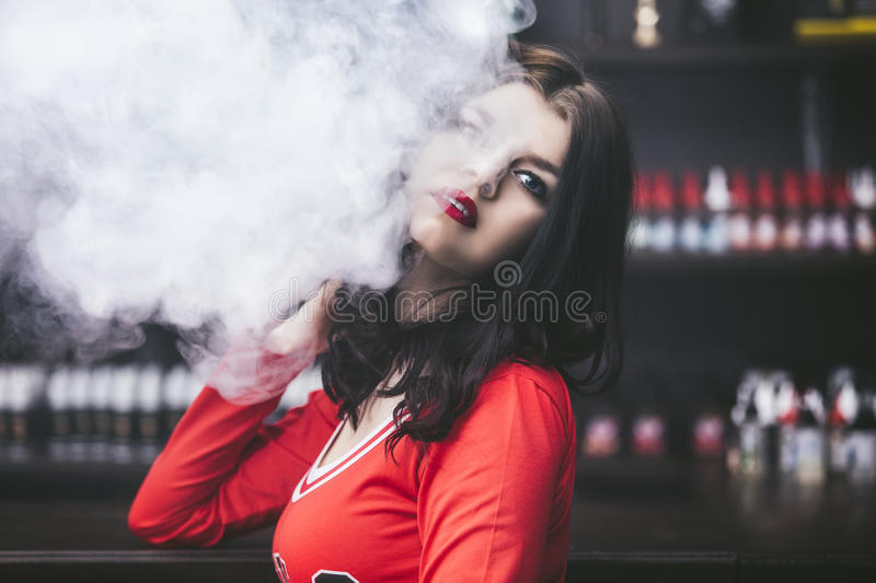 Young beautiful brunette woman with fashion makeup at the bar wi. Th a with vapor from electronic cigarette royalty free stock photos