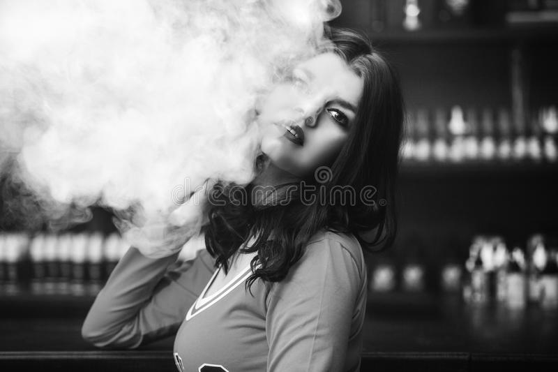 Young beautiful brunette woman with fashion makeup at the bar wi. Th a with vapor from electronic cigarette royalty free stock images