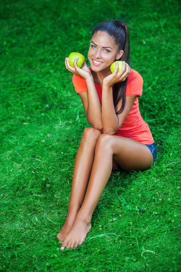 Young beautiful brunette woman holding two apples royalty free stock photo