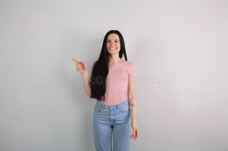 Young beautiful brunette woman with long hair standing by the grey background wearing jeans and pink shirt smiling and royalty free stock image
