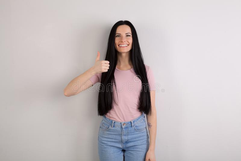 Young beautiful brunette woman with long hair standing by the grey background wearing jeans and pink shirt smiling stock images