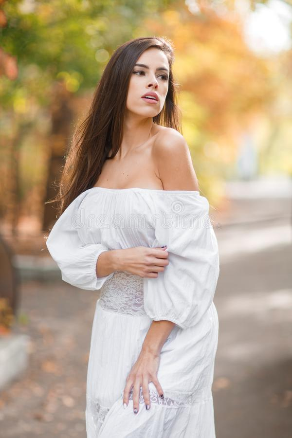 Beautiful young woman in a long white dress with dark brown hair posing outdoors on a blurred background. royalty free stock image