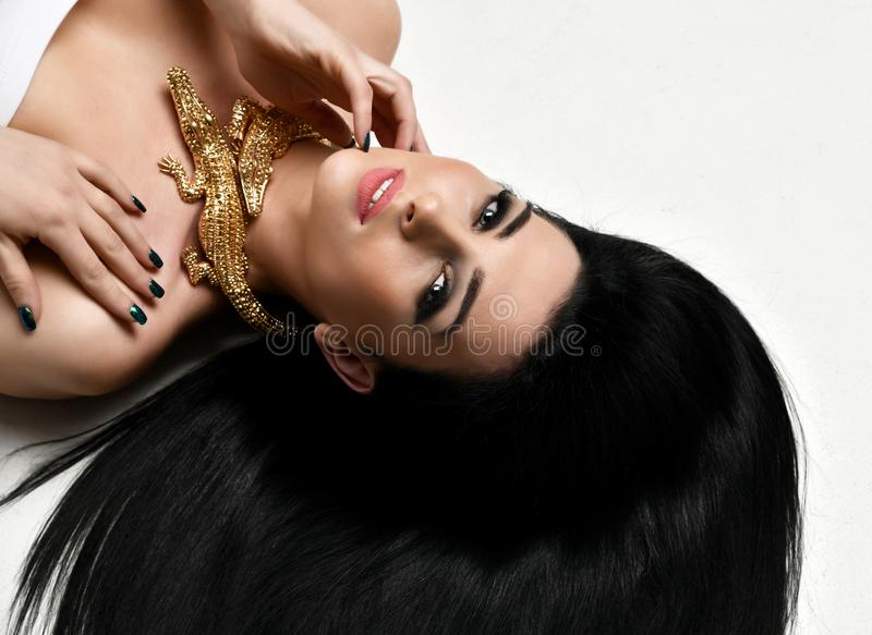 Young beautiful brunette woman lying on the floor wear expensive gold crocodile jewellery with long hair royalty free stock images