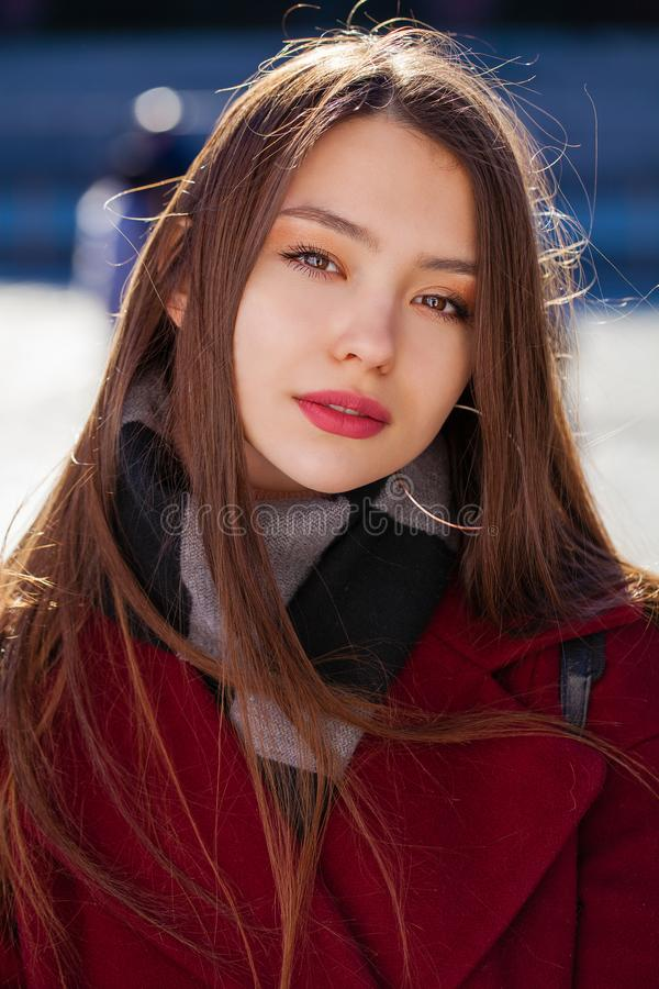 Young beautiful brunette woman in red coat posing on winter park royalty free stock image