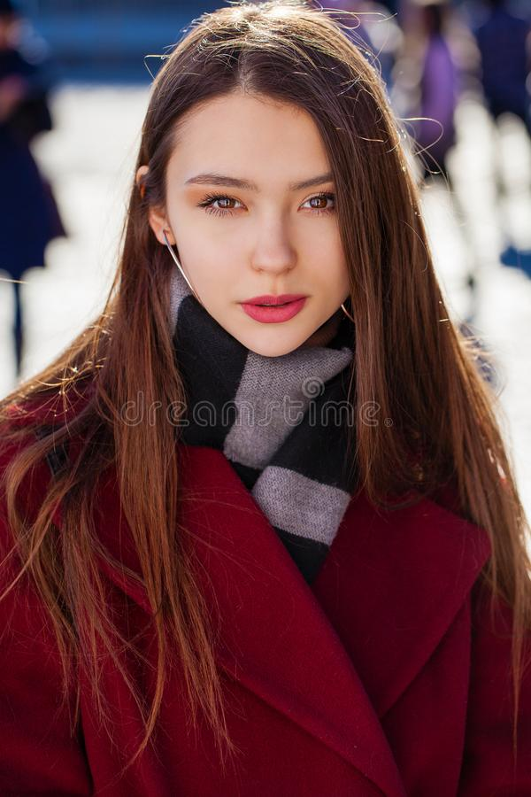 Young beautiful brunette woman in red coat posing on winter park royalty free stock photography