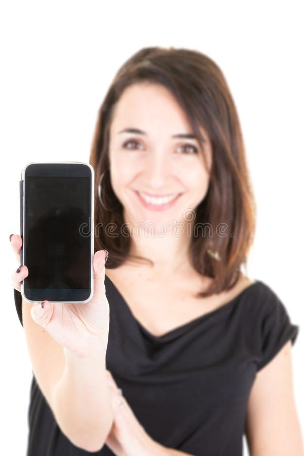 A Young beautiful brunette woman showing smartphone over white isolated background with happy face smiling royalty free stock images