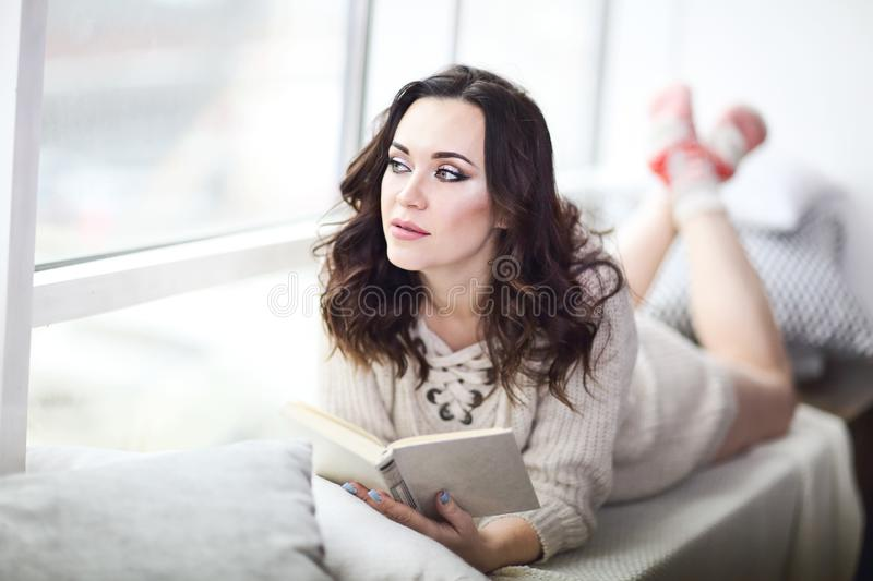 Young beautiful brunette woman  wearing knitted sweater reading book relaxing by the window royalty free stock photo