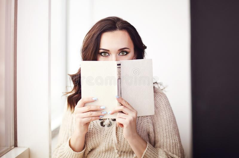 Young beautiful brunette woman  wearing knitted sweater reading book relaxing by the window stock images