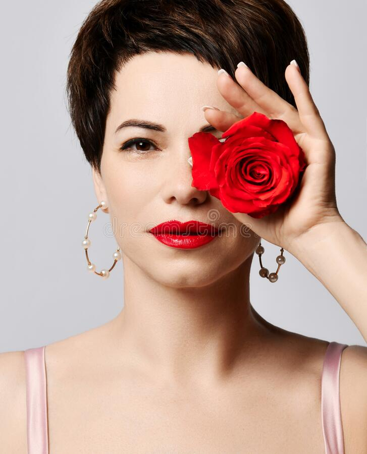 Free Young Beautiful Brunette Woman With Short Hair In Pink Silk Dress Holds Red Rose In Hand Covering Over One Eye Stock Photo - 194258370