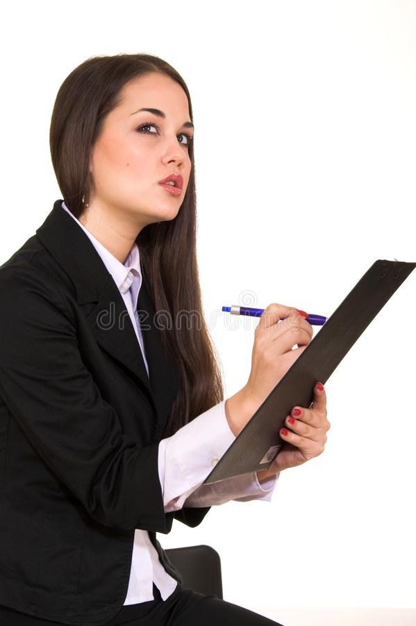 Young beautiful brunette holding scheduler and writing royalty free stock photography