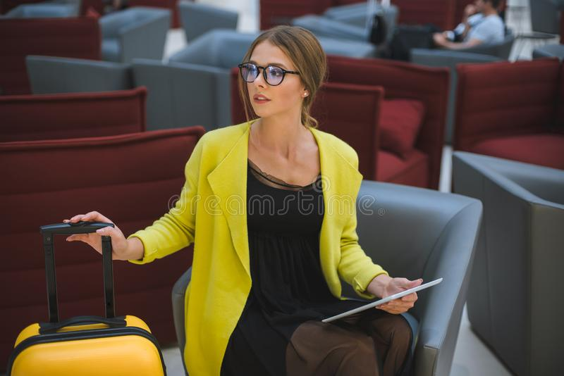 Young beautiful business woman in the airport lounge uses a smartphone and tablet. stock photo