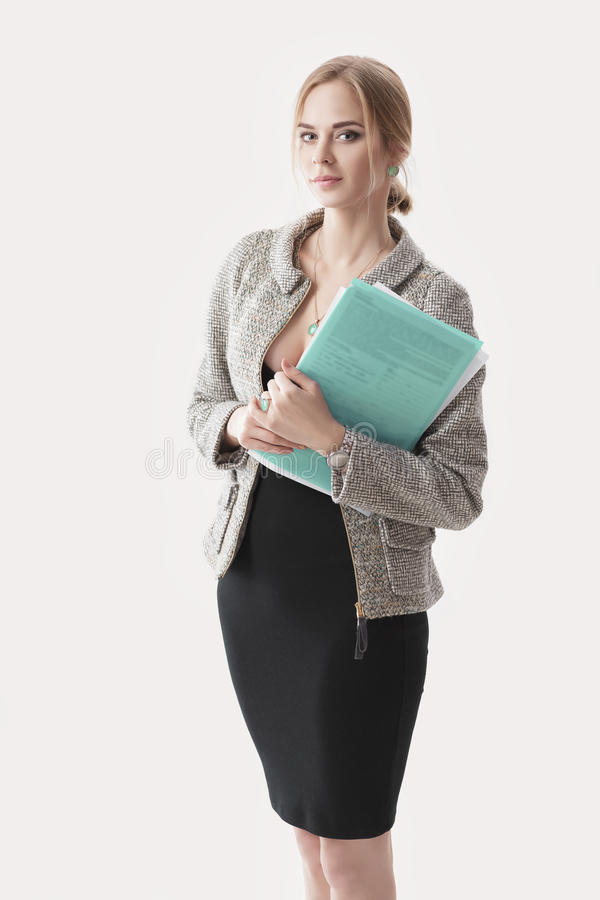 Young beautiful business woman in black dress, jacket holding folder of papers and smiling on gray background royalty free stock photo