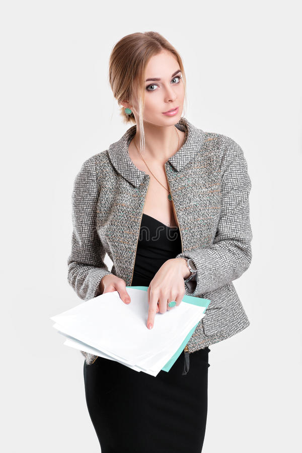 Young beautiful business woman in black dress, jacket holding folder of papers and smiling on gray background stock photos