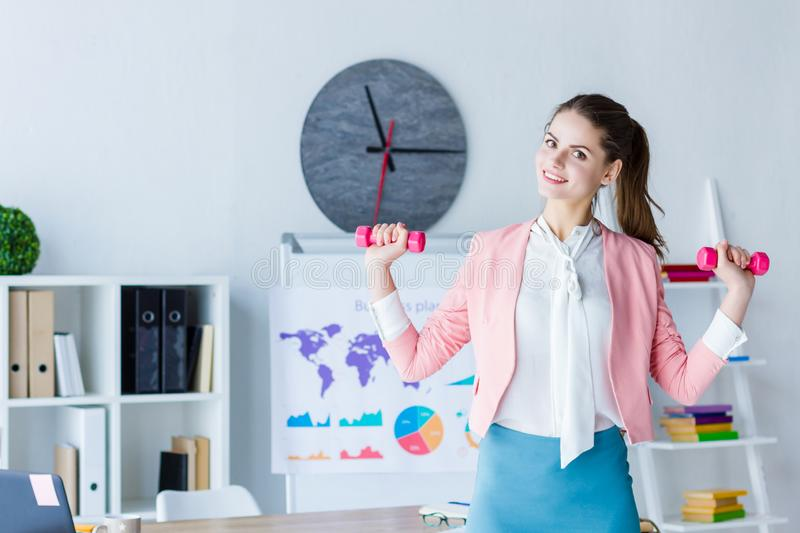 Successful business woman at modern office. Young beautiful business woman boss in pink blazer is doing exercises with dumbbells at workplace. Girl employee is stock photography