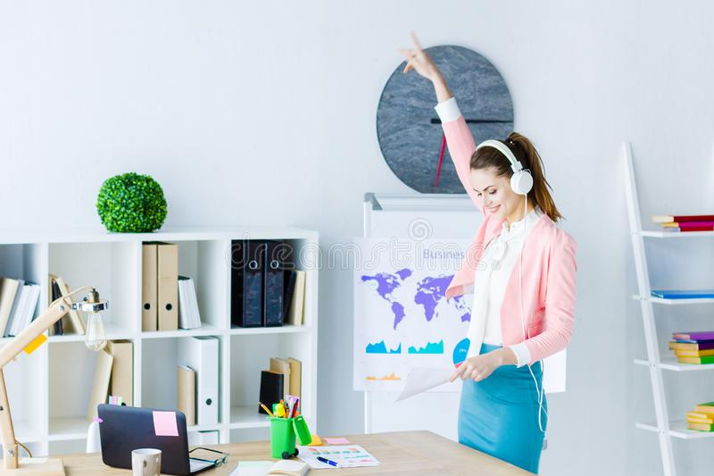 Successful business woman at modern office. Young beautiful business woman boss in pink blazer is listening music and dancing at workplace. Girl employee is royalty free stock image