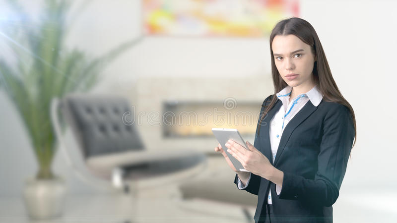 Young beautiful business woman and creative designer standing over blured interior background royalty free stock photography