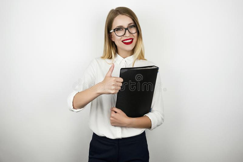 Young beautiful business woman in eyeglasses holding black folder with documents showing ok sign isolated white stock photos