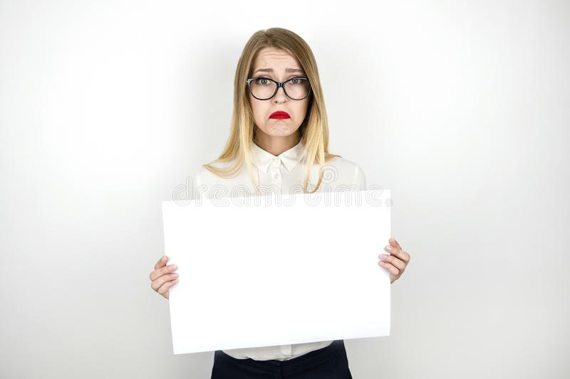 Young beautiful business woman in eyeglasses holding blank sheet of paper for announcement isolated white background stock photo