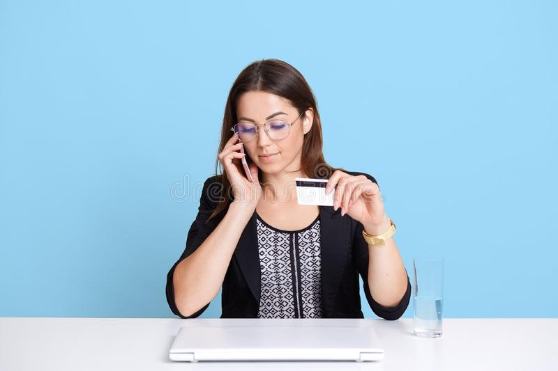 Young beautiful business woman has conversation via mobile phone and holding credit card in hand, using electronic device for royalty free stock images