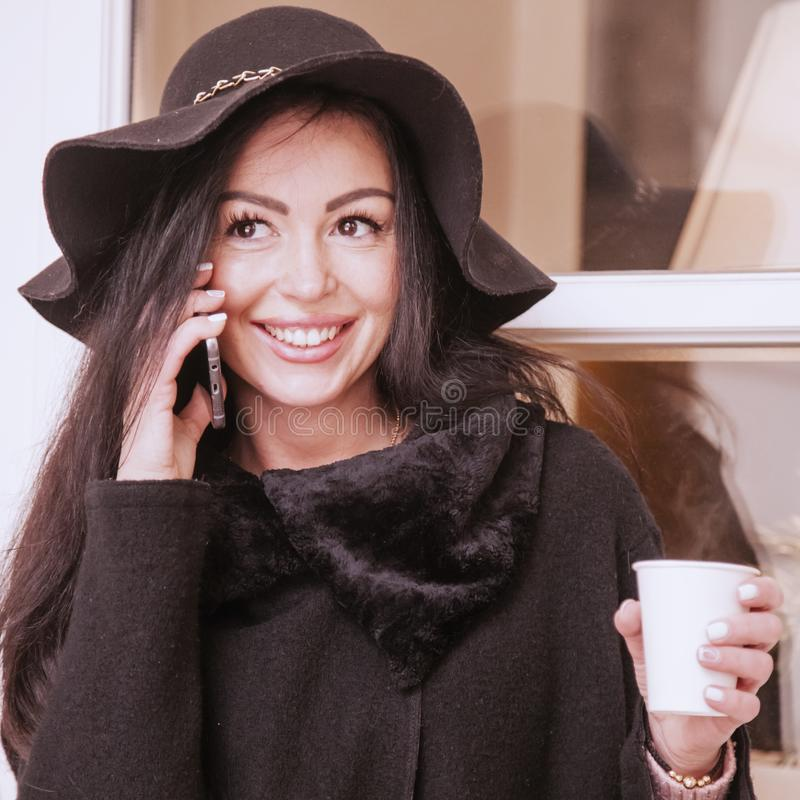 Young beautiful business woman holding  phone and a coffee royalty free stock image