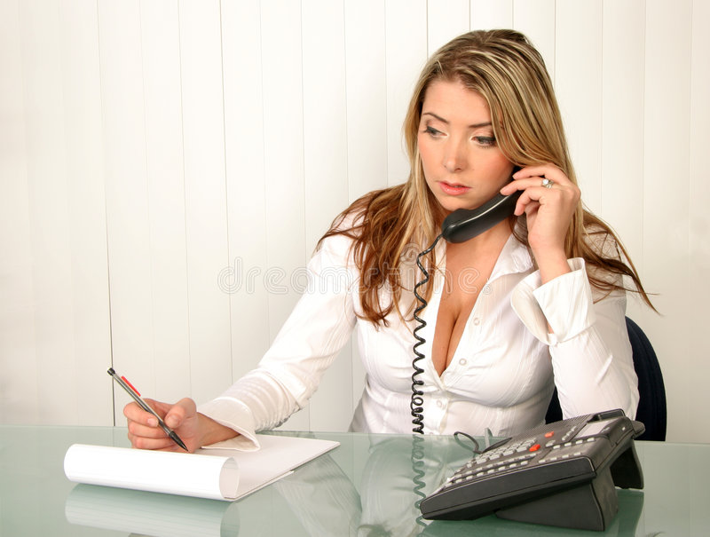 Young beautiful business woman holding phone and taking notes