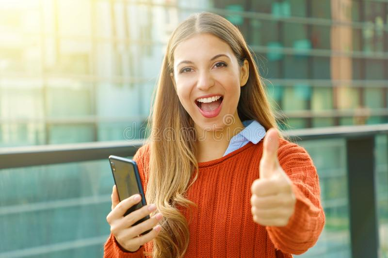 Young beautiful business woman holding smart phone showing thumb up on city street stock images