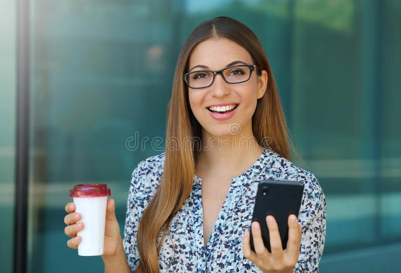 Young beautiful business woman outdoor with smart phone and coffee in her hands looks at camera royalty free stock photo