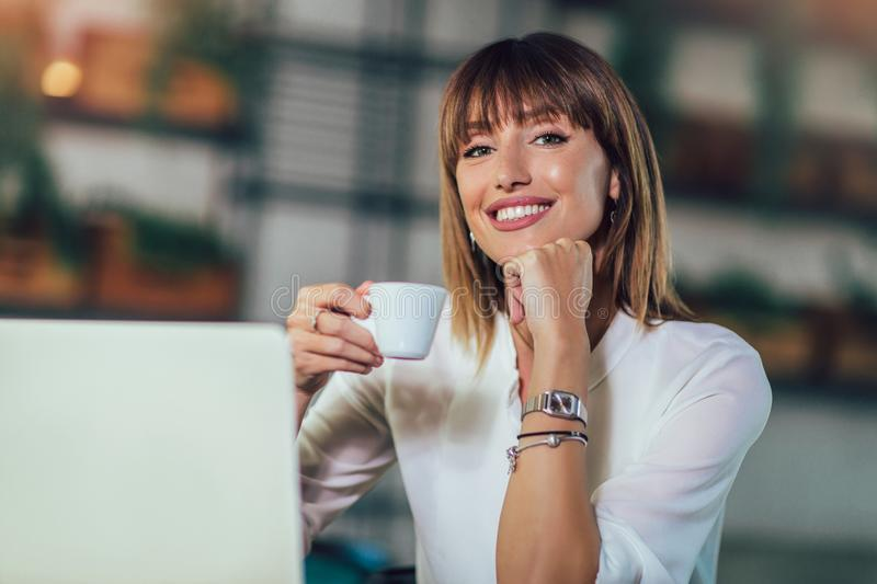 Young beautiful businesswoman enjoying coffee during work on portable laptop computer. Portrait of a young beautiful businesswoman enjoying coffee during work on stock photography