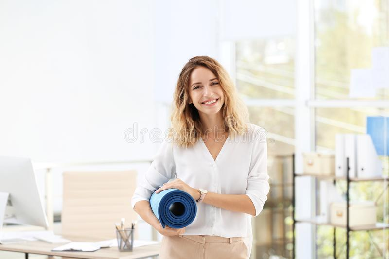 Young beautiful businesswoman holding yoga mat in office stock photos
