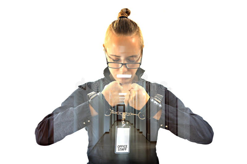 Young beautiful businesswoman with mouth shut with projection of office lamp as symbol scotch, prisoner of job in cuffs. Young beautiful businesswoman with mouth royalty free stock photos