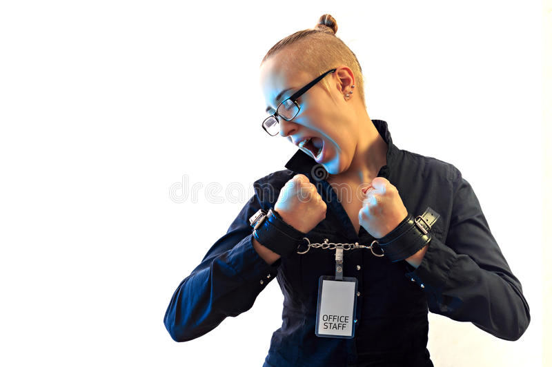 Young beautiful businesswoman screaming, prisoner of job in cuffs. Young beautiful businesswoman screaming with anger, prisoner of job in cuffs, horizontal view royalty free stock image