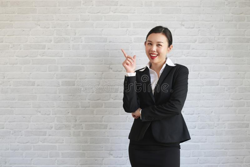 Young beautiful businesswoman smiling looking at camera pointing finger in side over white background stock images