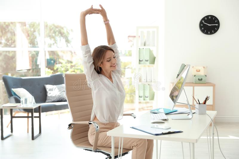 Young beautiful businesswoman stretching in office. stock photo