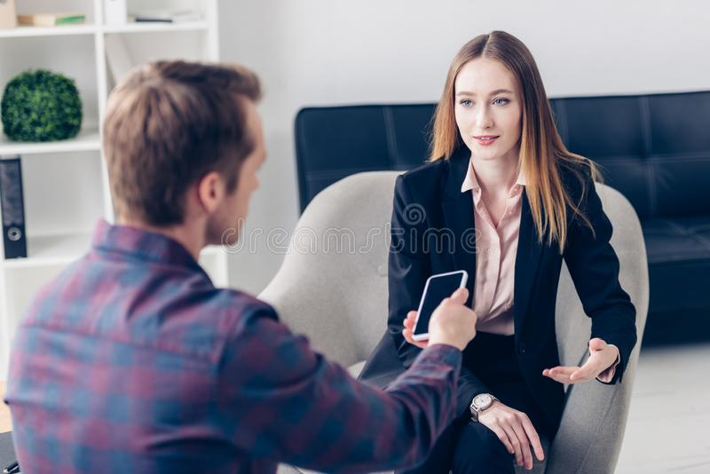 Young beautiful businesswoman in suit giving interview to journalist. In office stock images