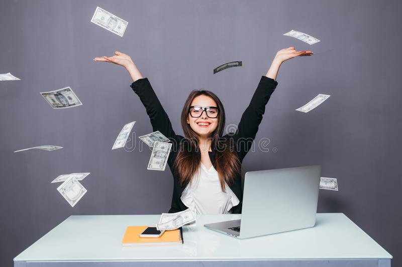 Young beautiful businesswoman throwing up money, sitting in office place with laptop stock photography